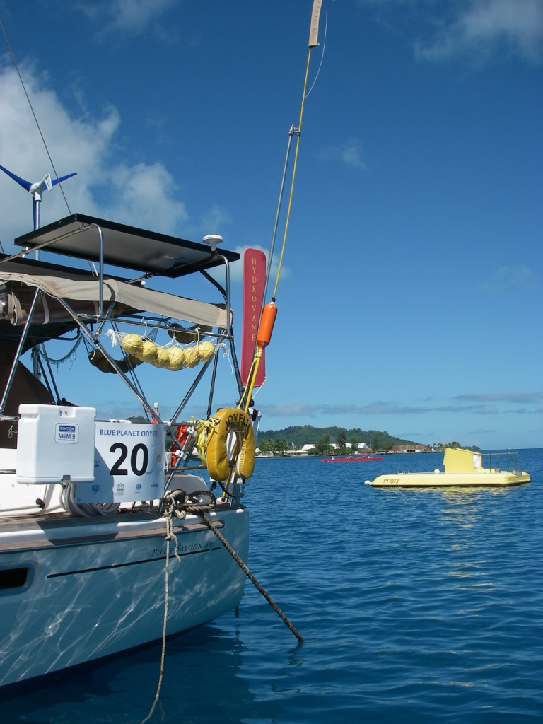 14. Joyful docked with a red outrigger canoe and a yellow submarine in the background in Bora Bora.