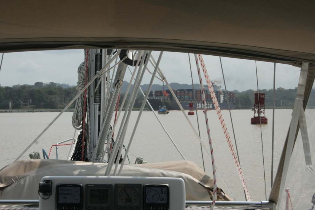 47a. Joyful motored in the Lake Gatun channel with Aventura in the lead, a container ship ahead, and channel buoys on the starboard side.