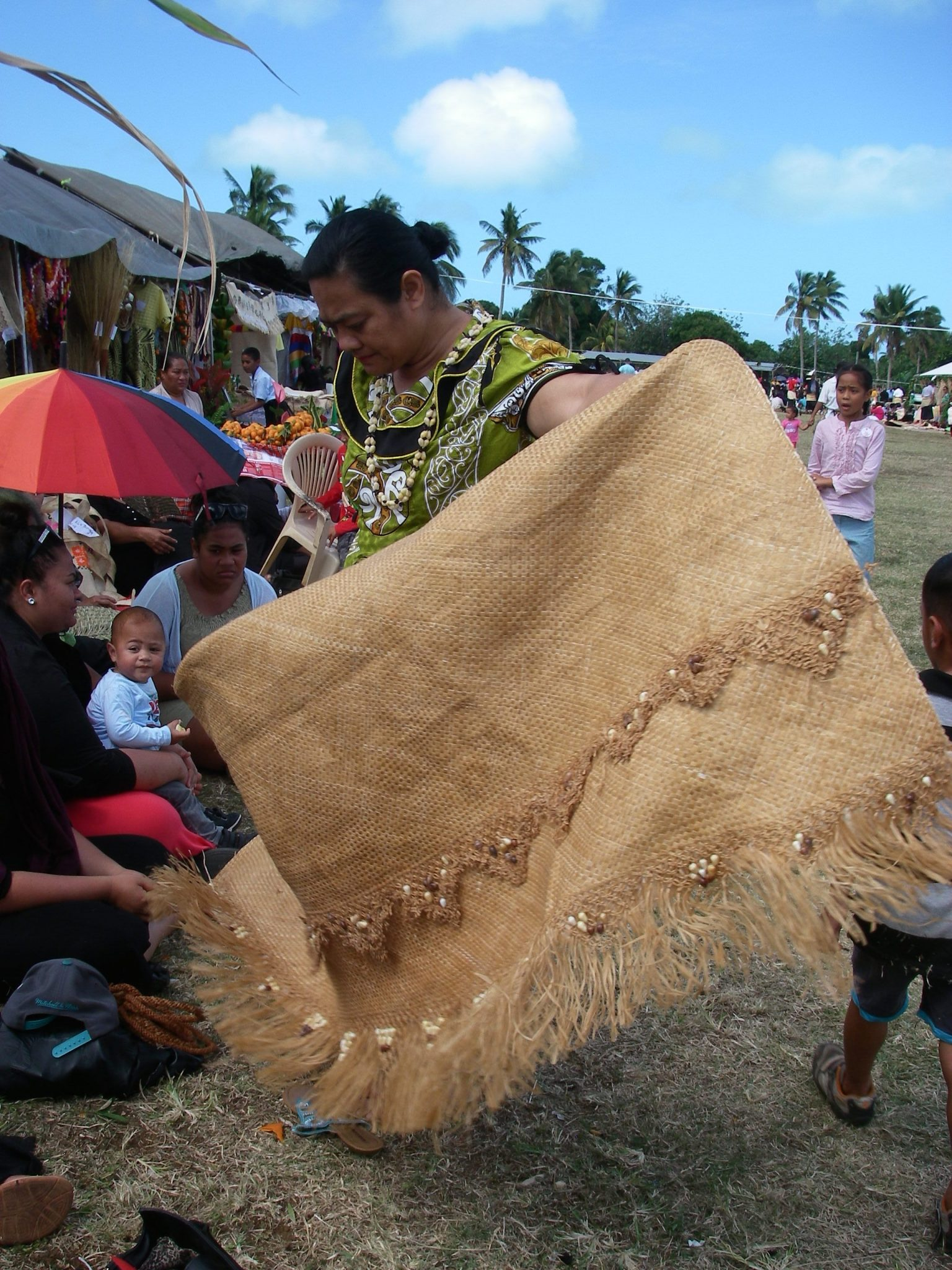 103. In preparation to show loyalty to the crown of Tonga when the King and Queen walked by, this Tongan woman gets her finely woven ta'ovala ready to wrap around her waist