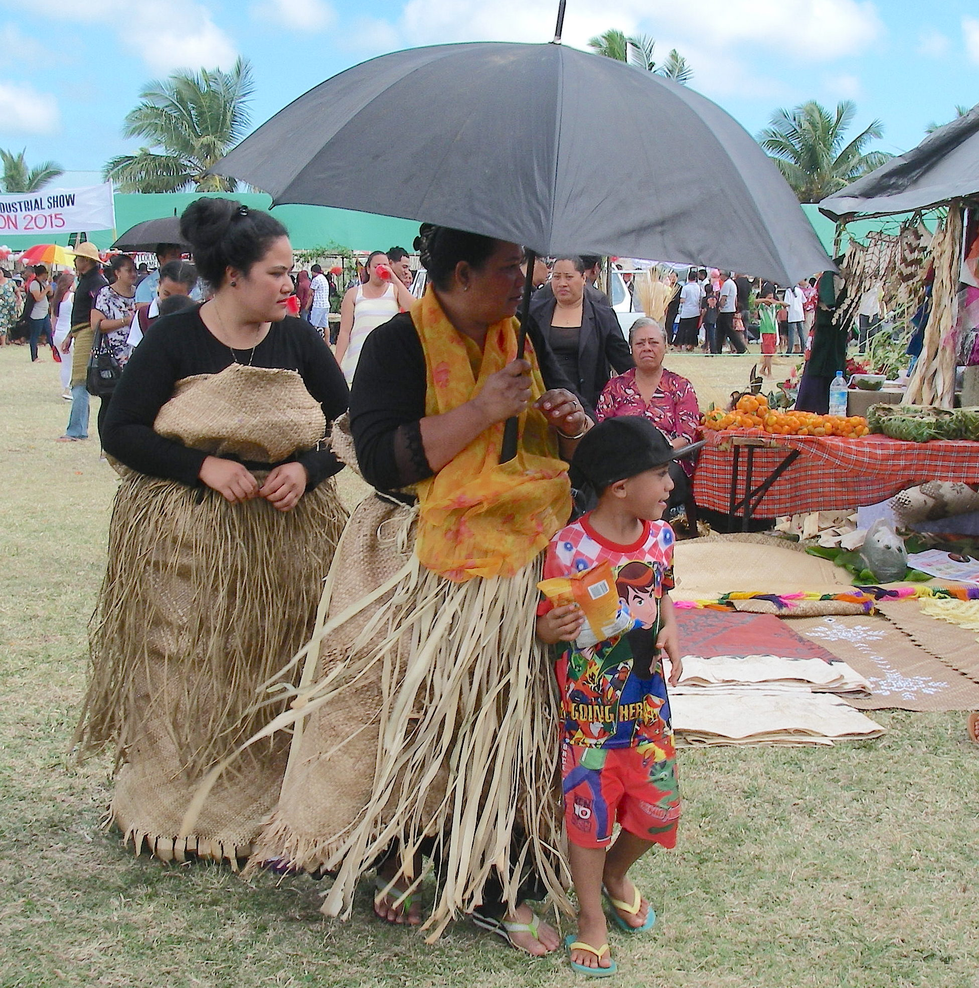 105. These two Tongan women are in mourning for a closely related loved one. This is evident by their black clothes, and their thick ta'ovala covered by a fakaaveave