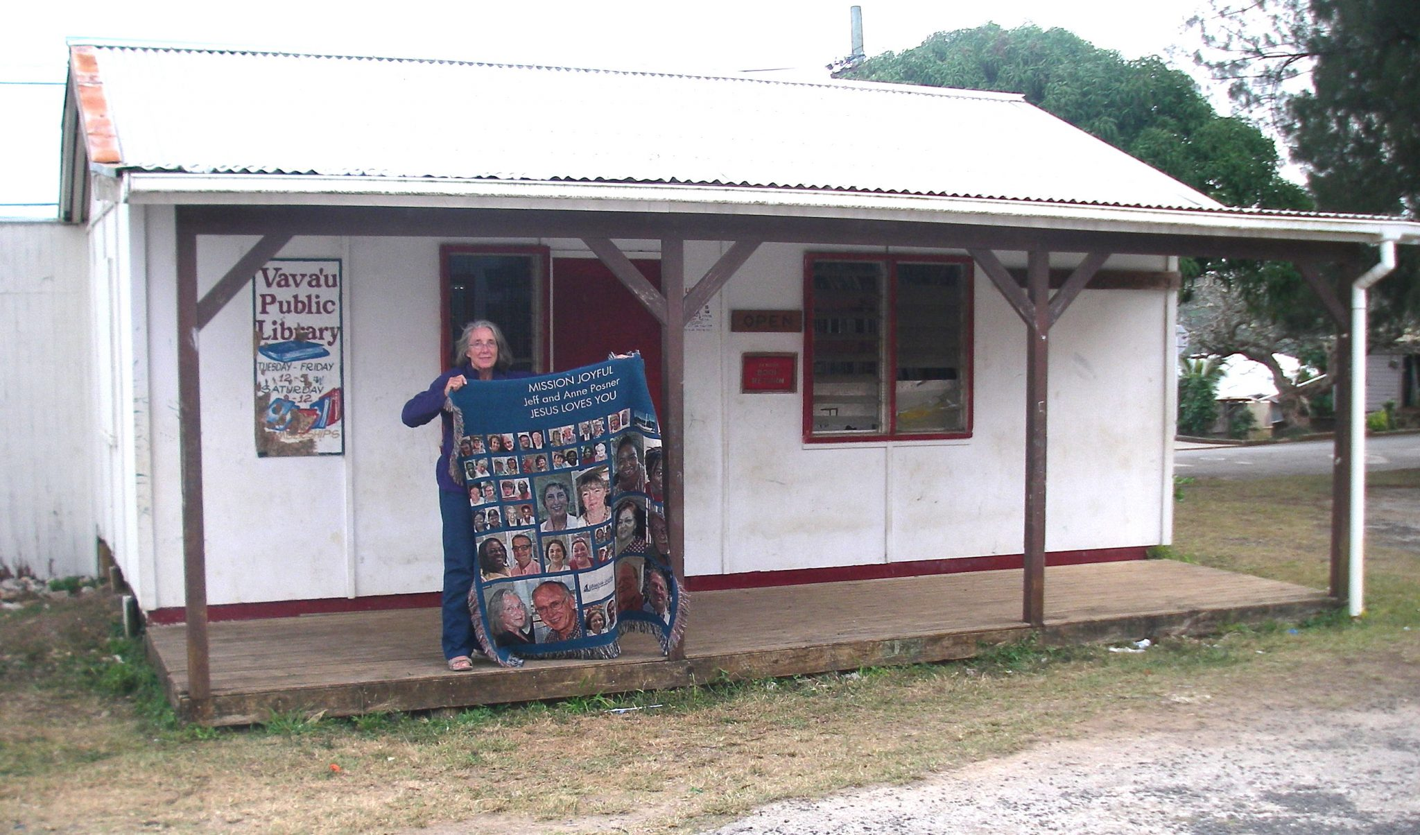 130. Anne in front of the Vava'u Public Library holding the Mission Joyful blanket given to Jeff and Anne from the Methodist Church chaple service in Huntsville, Alabama