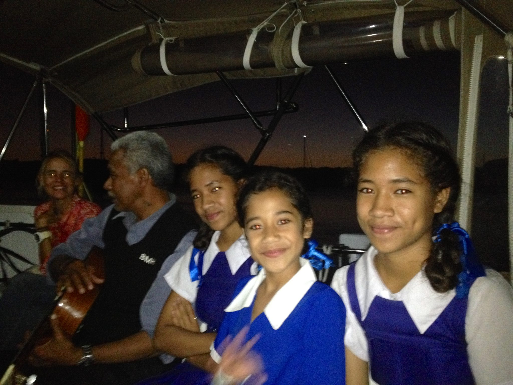 164. Tongan friends, Kilisitina, Otolose, and Tiara, their father, Soakai, and saling missionary friend Beatrice enjoy singing hymns at sunset from Joyful's cockpit!