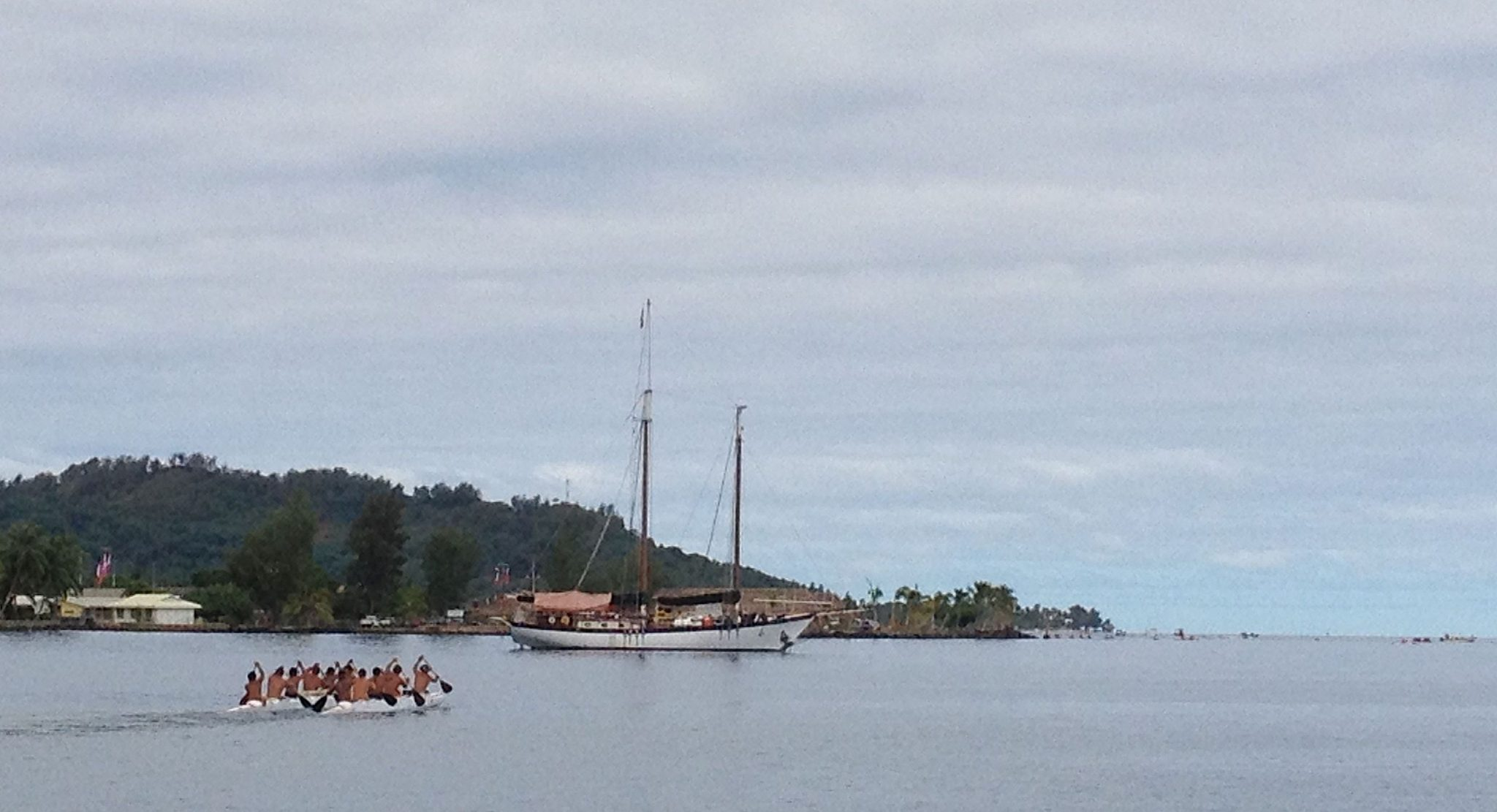 19. In a view from Joyful, a traditional outrigger canoe for 12 made its way to compete in the Heiva race in Bora Bora.  More competing outriggers were staged in the lagoon as seen on the right side of this photo