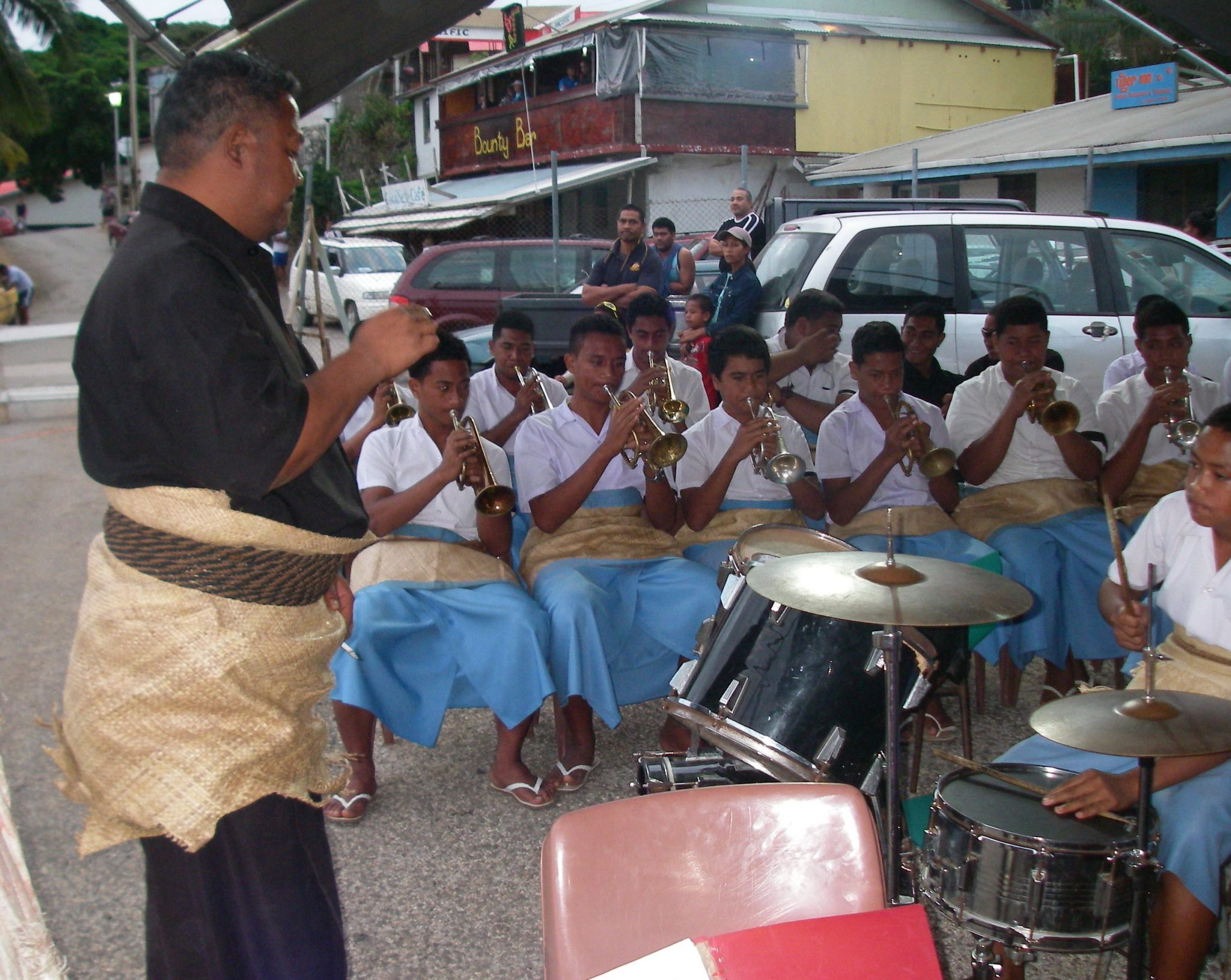 34. One of the local high school bands. The leader and the students are wearing the traditional woven hibiscus wrap showing allegance to the monarchy. The students also are wearing the wrap around pareas, their everyday uniform
