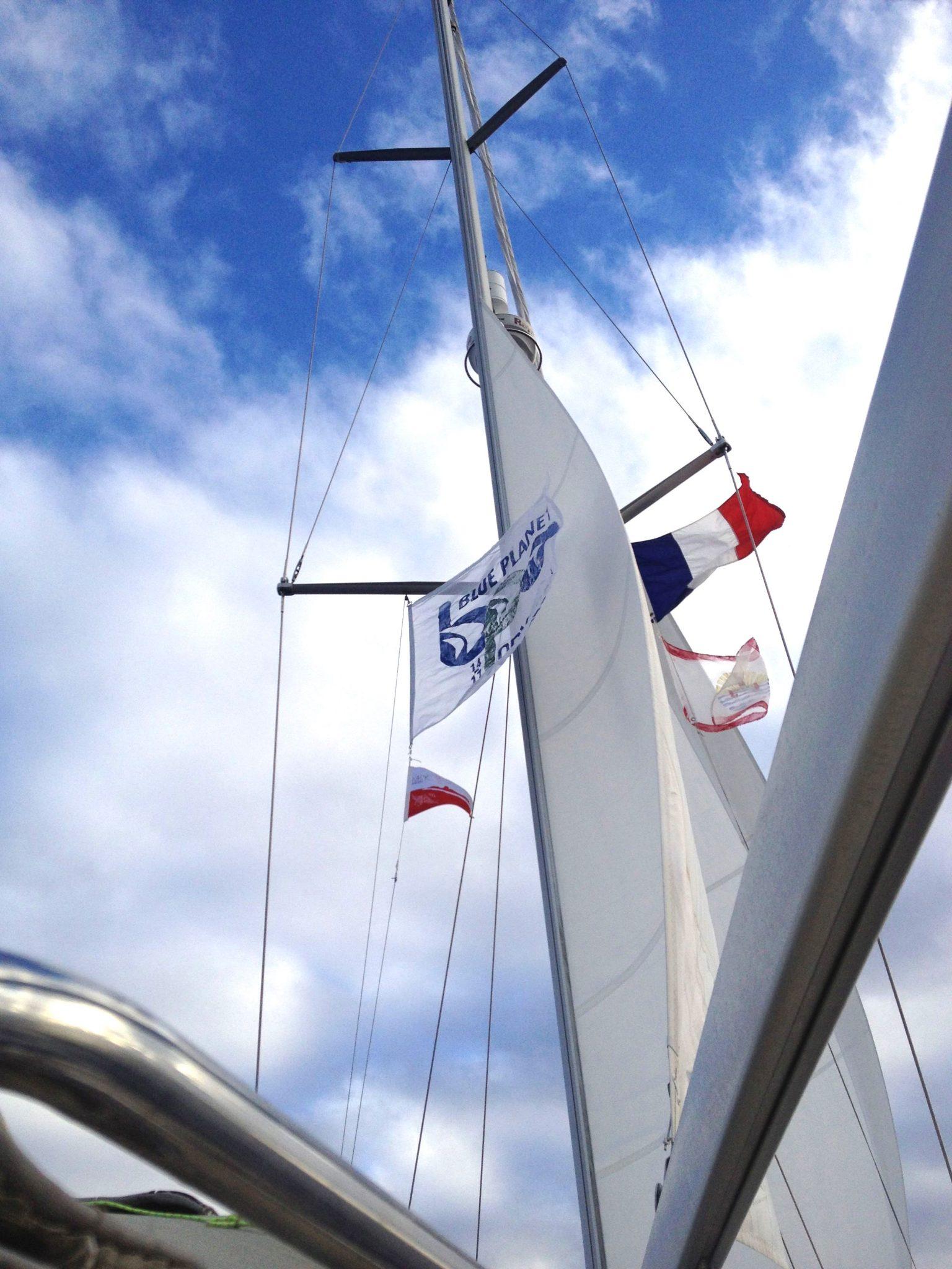 61. Joyful leaving Bora Bora flying the MaiKai Yacht Club Pennant, Blue Planet Odyssey flag, French Polynesia courtesy flag, and the French courtesy flag from her spreader halyards