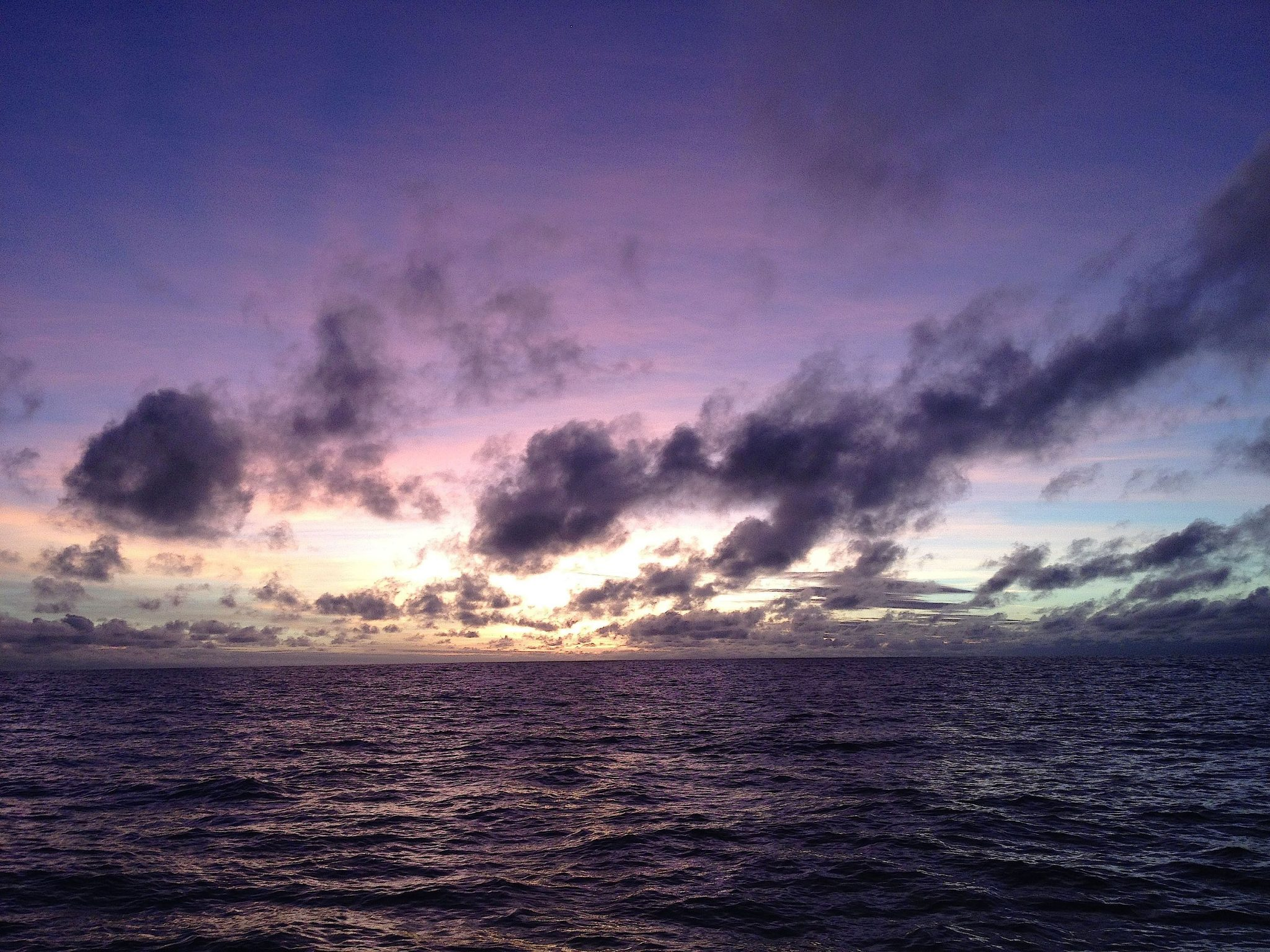 7. I took this photo a few minutes after the previous photo about a minute after the sun dipped below the horizon, changing the sky's hue to vilot. Joyful was sailing westbound from Bora Bora to Vava'u, Tonga