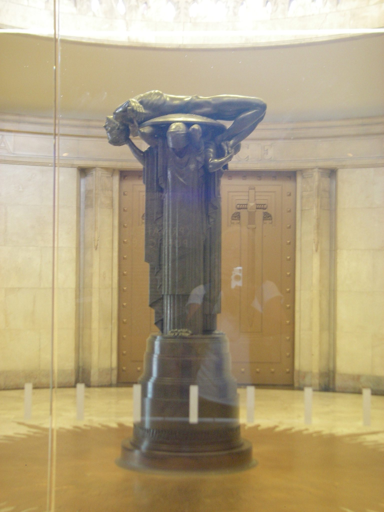 105. The sculpture depicts a fallen ANZAC warrior returning to his land in glory, in the manner of an ancient Grecian soldier, carried on his shield and sword, supported by wives, mother